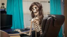 A (fake) skeleton sits at an office desk, wearing a long wig and smiling at the camera.