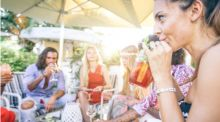 A young woman sits with a group of friends outside, drink in hand.