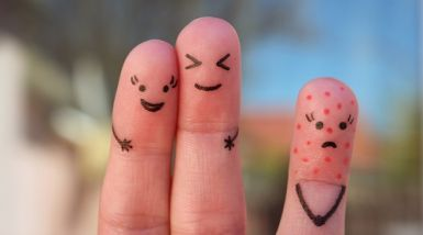 Three fingers are held up to the camera, with faces drawn on them. Two stand together with smiley faces, one sits apart covered in red dots and a sad face.