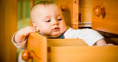 baby reaching into an open draw on a wooden cabinet
