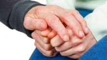 A hand rests supportively on the hands of a patient