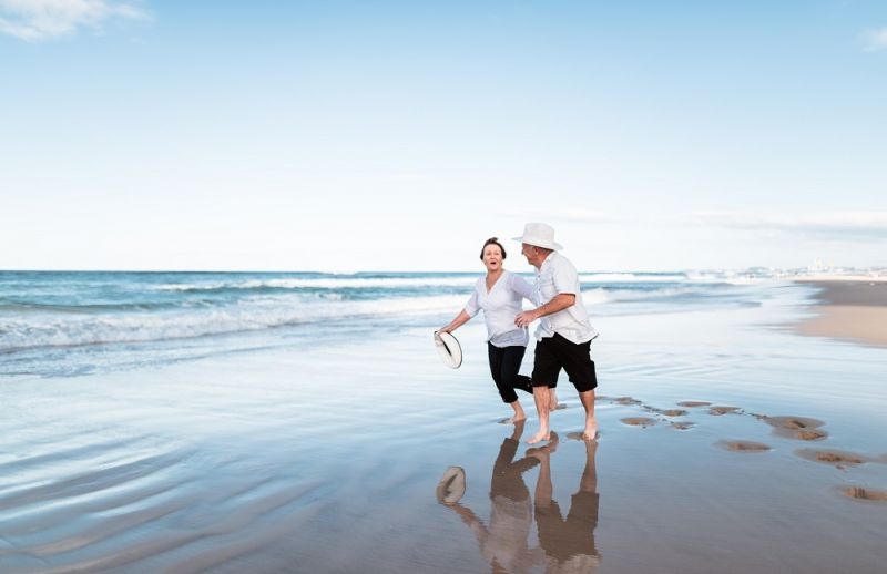 An older couple run happily down a beach.
