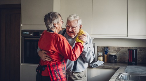 An older couple dance together in their kitchen.