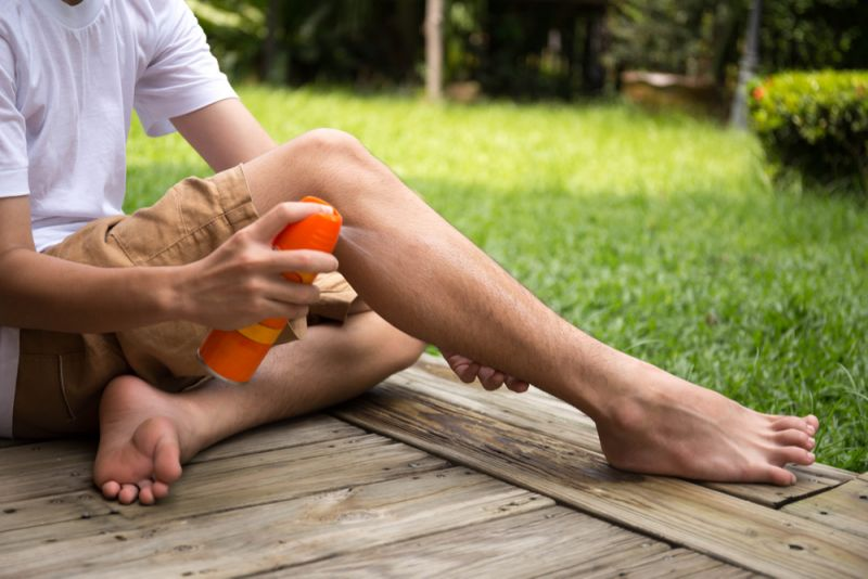 A young boy sits on his deck, spraying his legs with mosquito repellent.