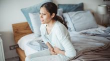 Woman sitting on edge of bed, holding abdomen in pain