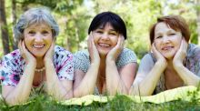 Three middle aged women lie in the grass in a park, resting their chins on their hands, smiling at the camera.