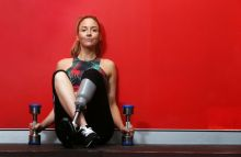 Lisa Cox sits on the floor, against the wall of a gym, holding dumbbells in each hand.