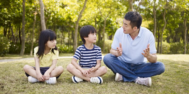 A father sits on the grass and talks to his two children.