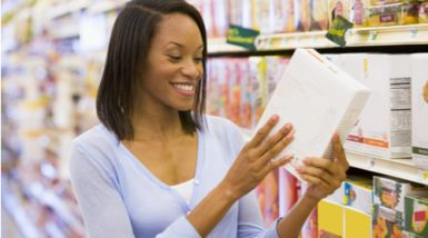 A woman stands in the grocery store, reading hte infor