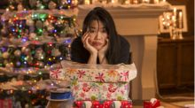 A woman sits with her elbow resting on top of a pile of wrapped Christmas presents, her chin on her hand, a tired expression on her face.