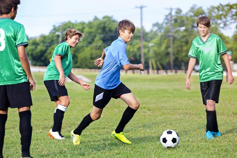 Four teenage boys play soccer on a field.
