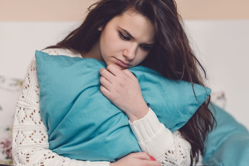 A teenage girl holds a pillow and looks unwell