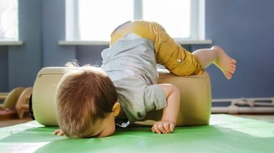 A toddler falls over onto a soft mat