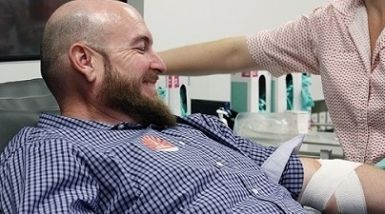 A man smiles as a nurse wraps a bandage around his arm after he has donated blood.