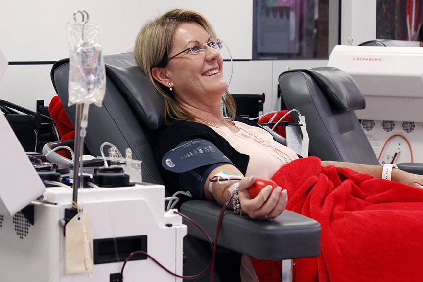 A lady smiles while lying on a medical armchair, donating blood.