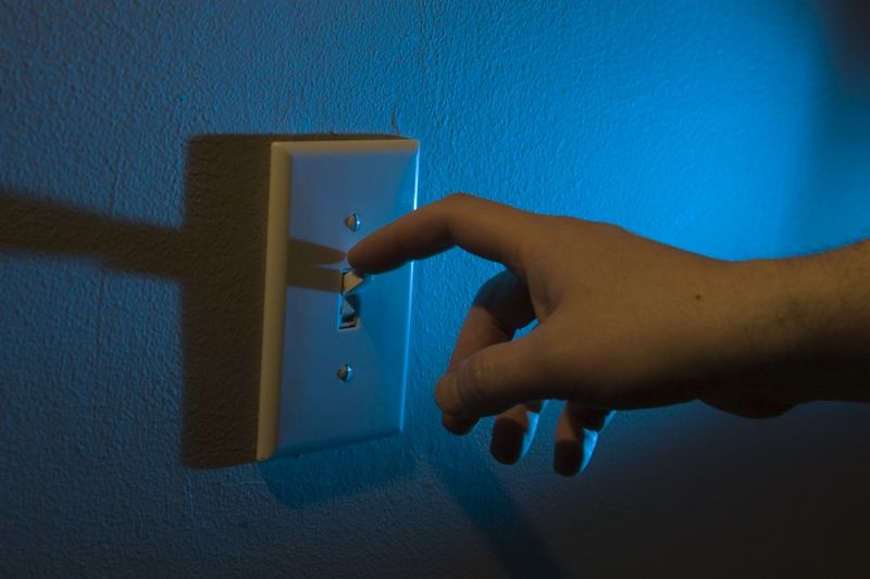 A man's hand on a light switch.