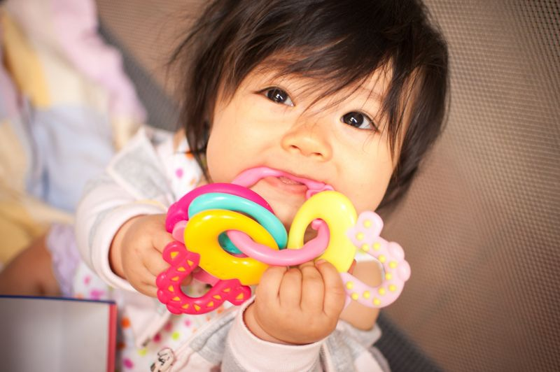 A baby chews on a teething ring
