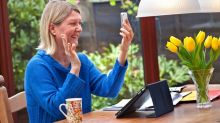 A woman sits in her garden and waves at people she is video calling on her phone.