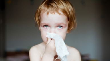 A toddler stands with a tissue to her face, looking cheekily at the camera.