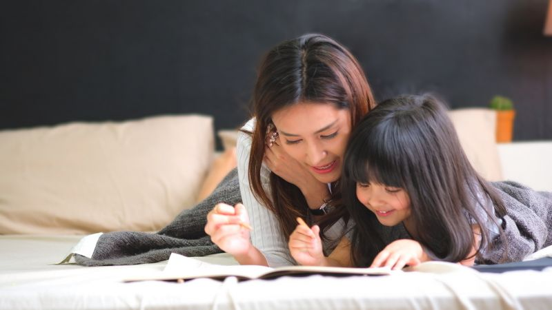 A mum and daughter lie on a bed writing a letter.