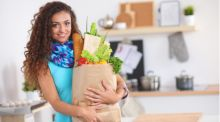 A young woman stands in her kitchen, holding a paper bag filled with vegetables and fruits.